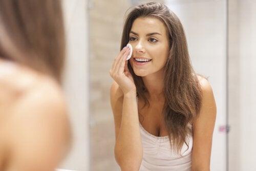 Nainen puhdistaa kasvojaan