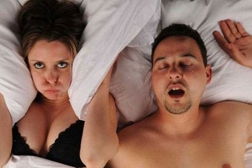 A man snoring in bed next to a woman.