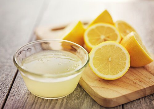 Bowl of lemon juice with cut lemons