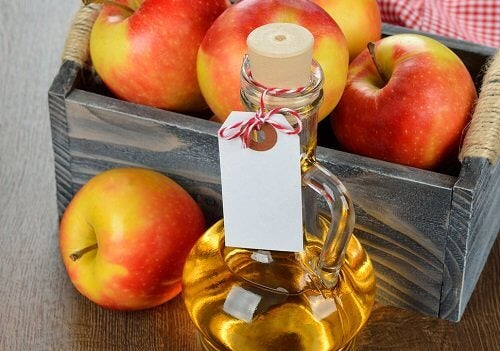 Apple cider vinegar with box of apples