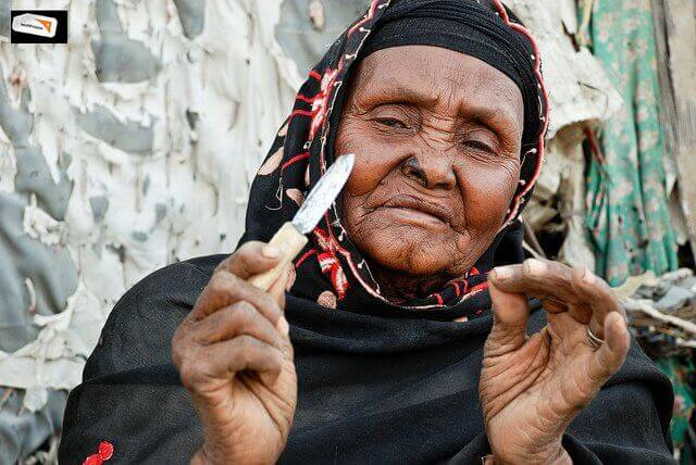 Woman holding a blade used for clitoral circumcision