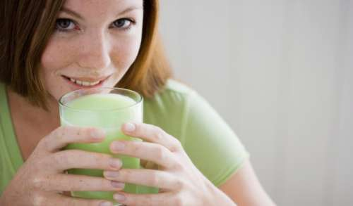 Woman drinking smoothie made with artichokes