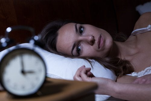 Woman staring at an alarm clock. not able to sleep