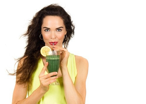 Woman drinking a green juice to strengthen her veins