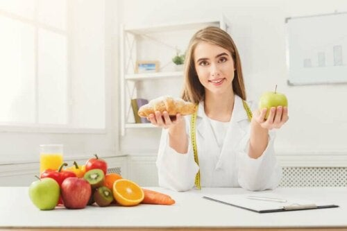 A doctor holding fruits to include in the diet other than an orange.