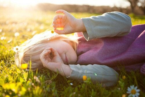 Tyttö makaa nurmikolla