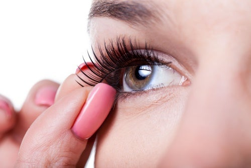A woman adjusting a fake eyelash.
