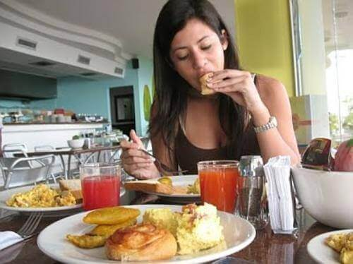 A woman overeating and eating many unhealthy foods