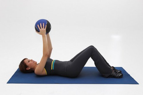 Woman doing yoga exercise with ball on mat