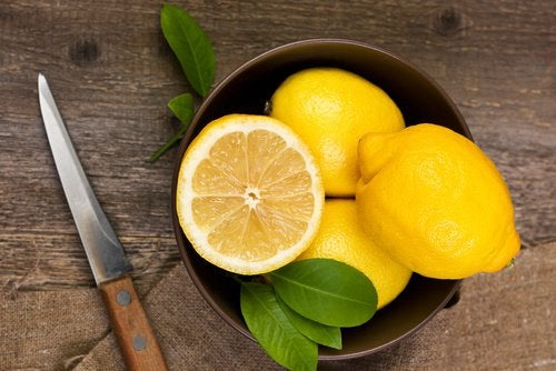 A bowl with whole and cut lemons.