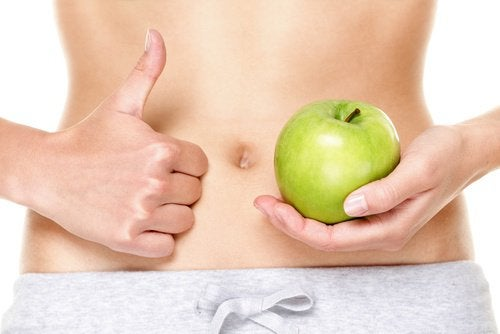 Holding an apple next to a flat belly