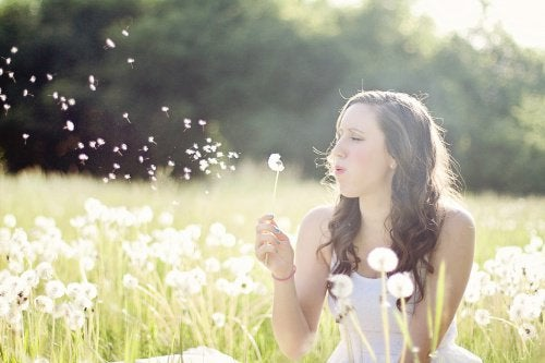 Woman sitting in a field blowing a dandelion flower, caring for herself
