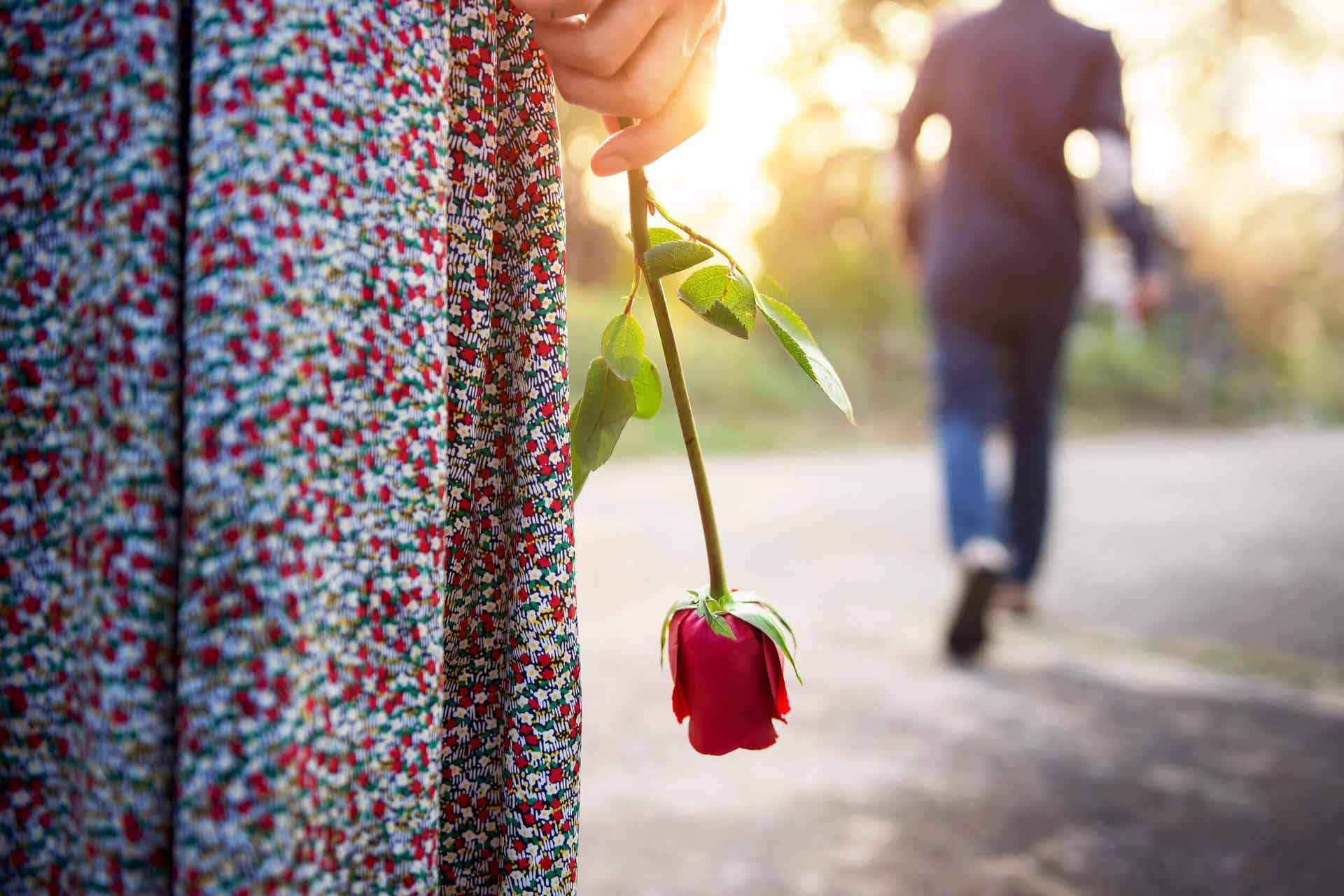 A man walking away from a woman holding a rose down by her side.