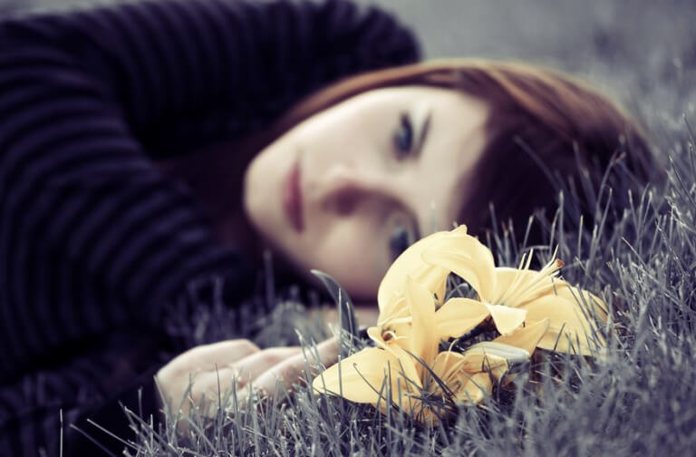 Girl laying in grass with depression