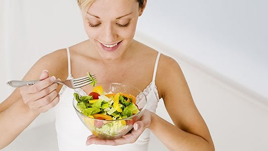 Woman eating a salad trying to eat healthily