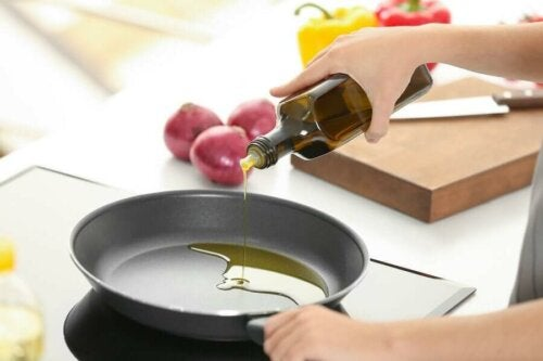 A woman cooking with healthy olive oil.