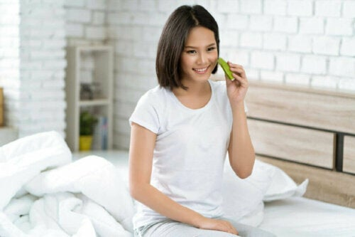 woman applying aloe vera to her face sitting on her bed smiling
