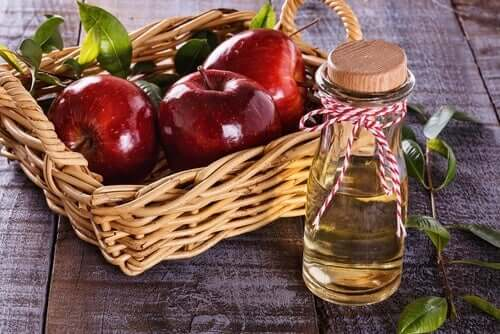 A bottle of apple cider vinegar and a basket of apples.