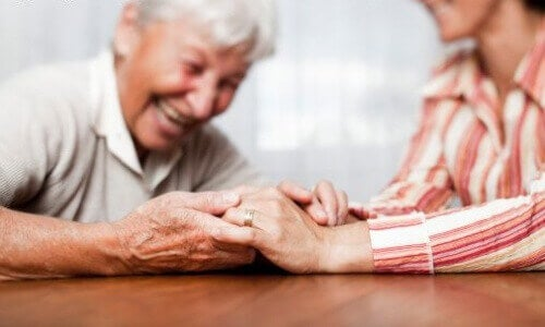 Old couple holding hands on table caretaker and patient