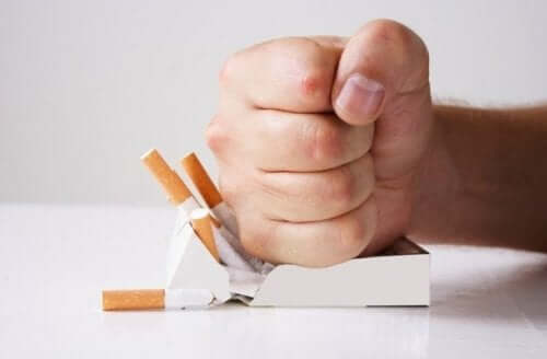 A hand crushing a box of cigarettes.