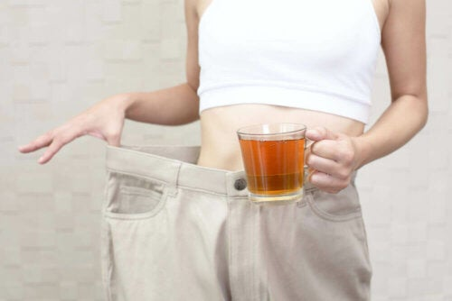 A woman with a cup of tea that serves to burn fat and reduce abdominal bloating.