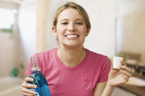 A woman using mouthwash.