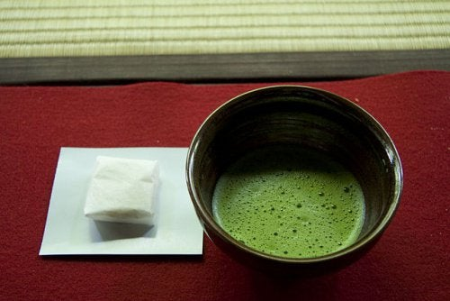 A bowl of green tea next to some packets.