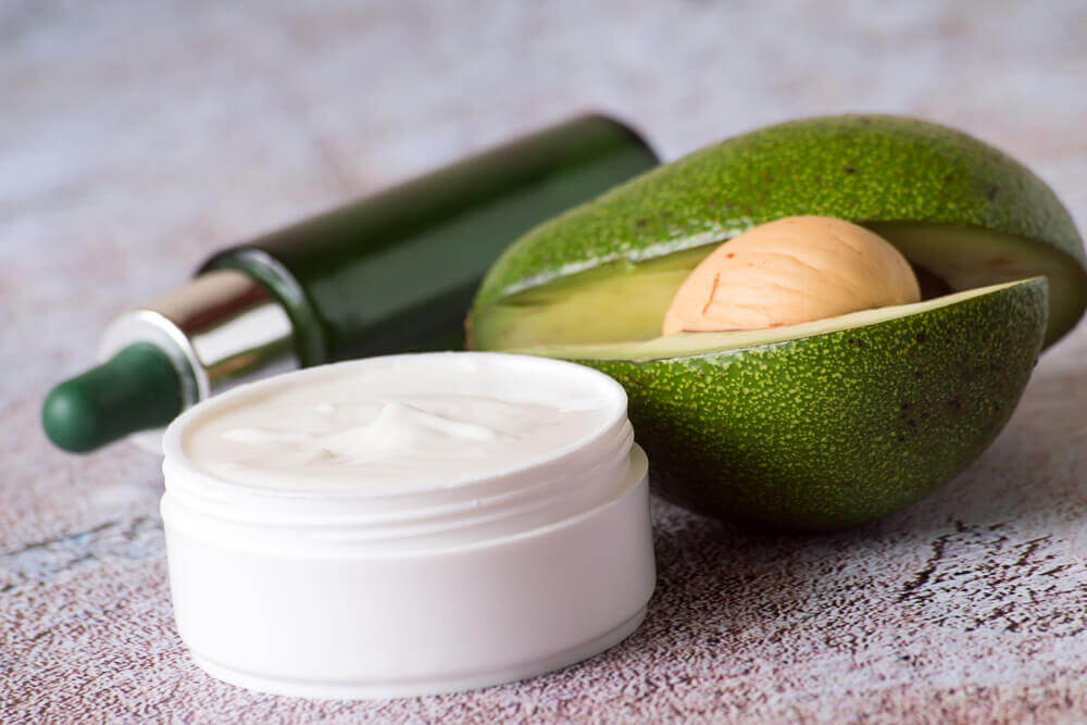 A small jar of lotion next to an avocado.