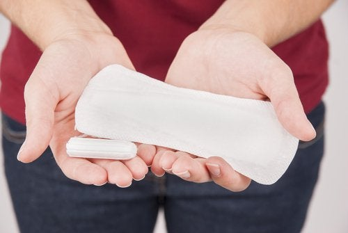 woman holding a tampon and a pad