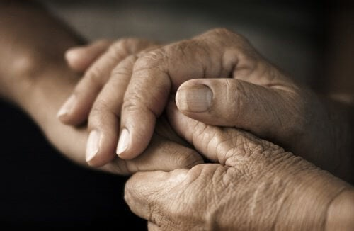 Elderly person holding a young person's hand