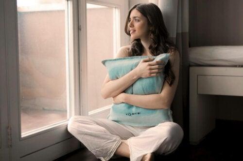 A woman hugging a pillow.