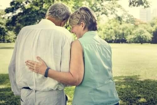 An elderly couple walking in the park.