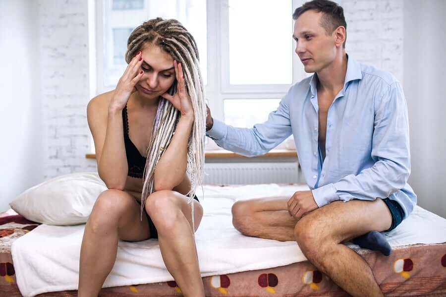 A couple sitting in bed having a hard time talking about sex.