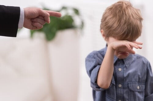boy crying with dad pointing finger at him, parenting