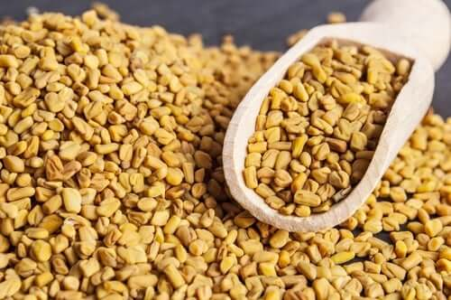 Fenugreek seeds with a wooden scoop.