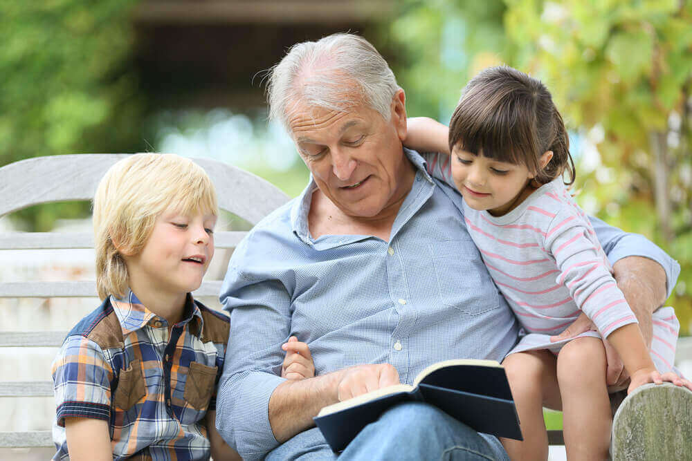A grandfather reading to his grandchildren.