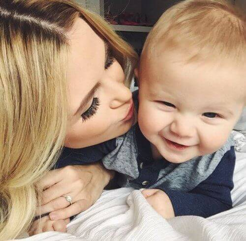 Blond mother kissing baby son on the cheek
