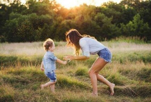 Mother and son playing in field during sunset having a son