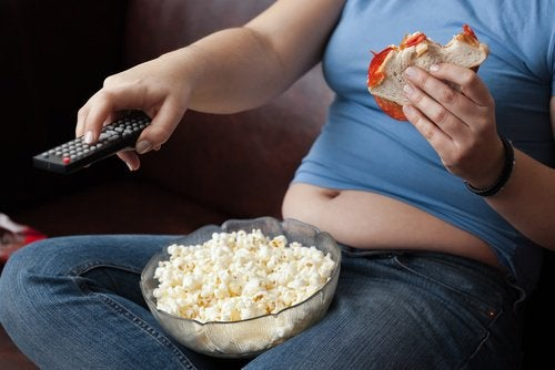 Woman eating junk food and watching television