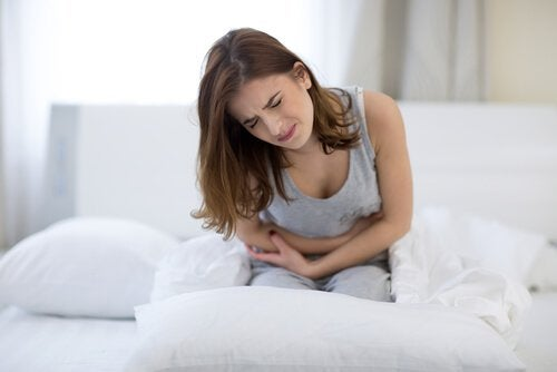 Woman in bed leaning over in pain painful period symptoms of endometriosis