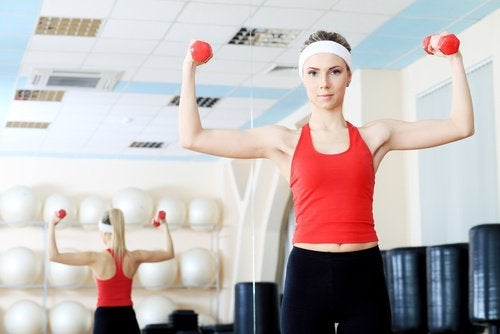 Woman lifting hand weights in a gym as treatments for sagging breasts