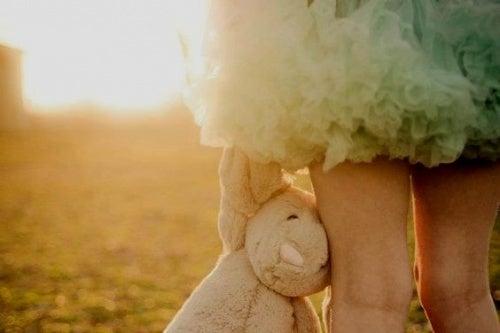 young girl holding stuffed animal
