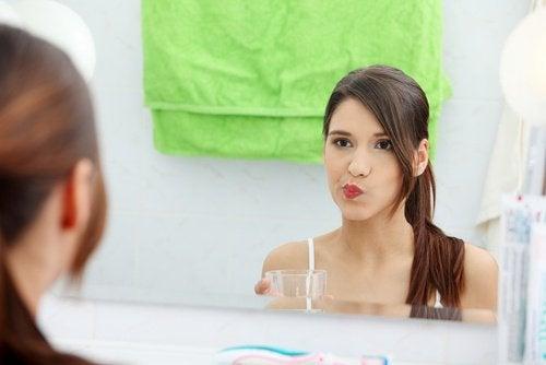 A woman using mouthwash.