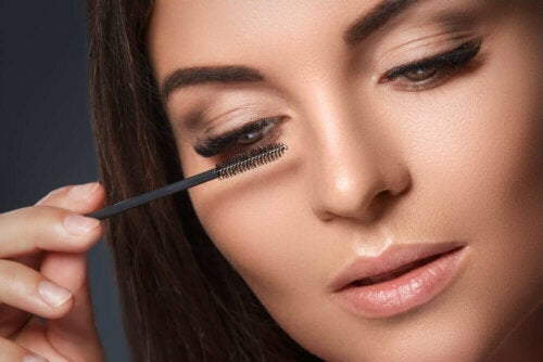 A woman with droopy eyelids putting on mascara.