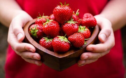 A woman holding a bowl of strawberries.