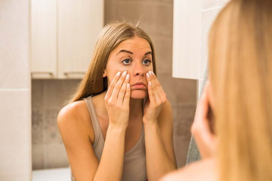 A woman looking at the dark circles under her eyes in the mirror.