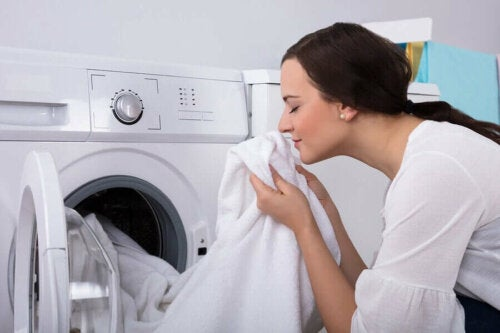 A woman sniffing fresh white laundry.