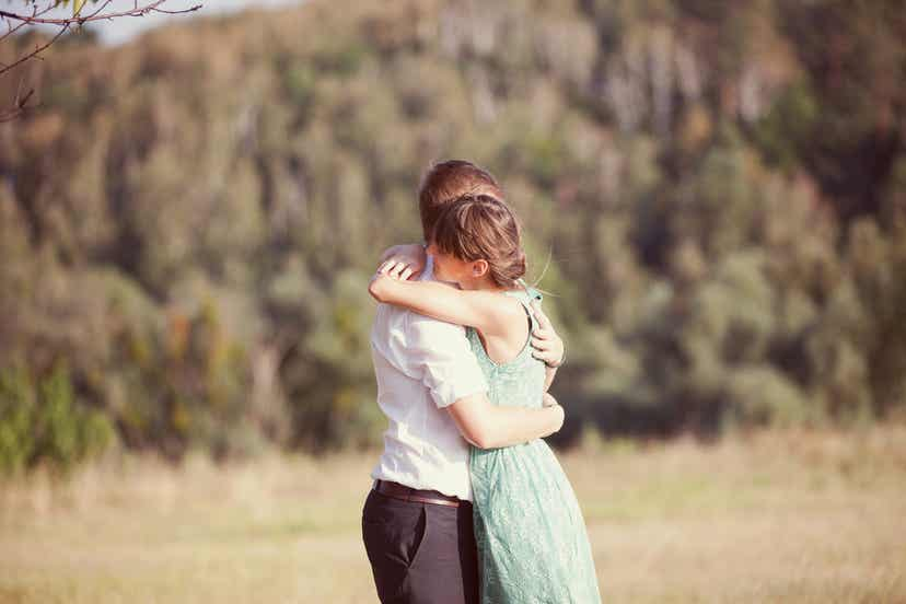 A couple embracing in a field.