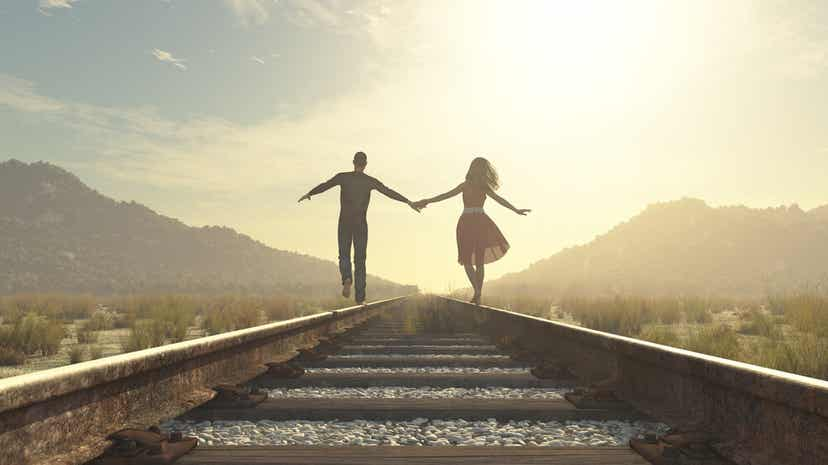 A couple holding hands while walking down a railroad track.