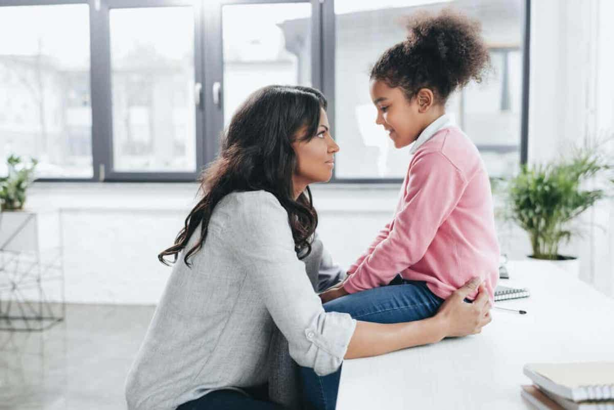 A mother talking with her young daughter.